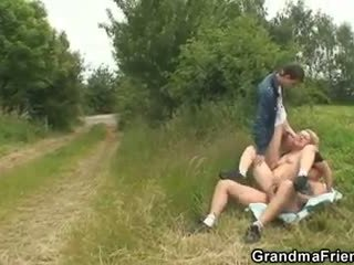 Slutty oma takes two cocks in de fields