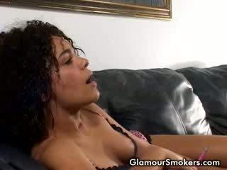 Tumšs haired prostitūte lying uz the divāns smēķētāji cigarettes