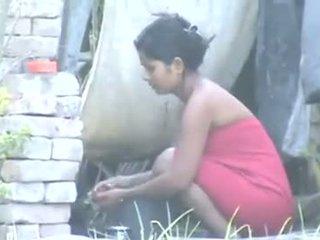 Ινδικό χωριό κορίτσι κάνοντας μπάνιο outdoors