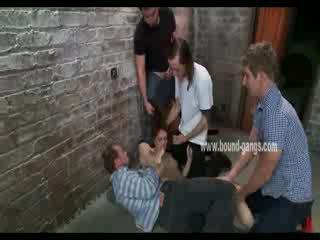 Brązowy haired i posłuszne lalka gets brutally handled przez a bunch z napalone men