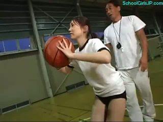 Escolar en entrenamiento vestido fingered por la entrenador en la baloncesto entrenamiento