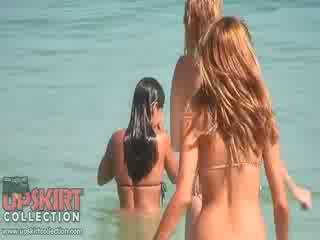 La cutie dolls en sexy bikinis are jugando con la waves y getting spied en