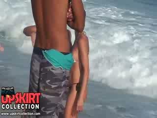 De warm zee waves are gently petting de bodies van schattig babes in heet sexy swimsuits