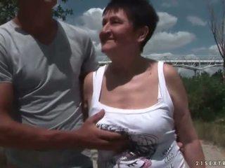 Krūtinga močiutė dulkinimasis jos jaunas boyfriend lauke