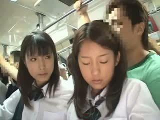 Two schoolgirls ग्रोप्ड में एक बस