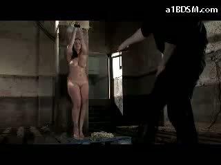 Krūtainas meitene ar tied arms whipped kamēr ūdens falling līdz viņai uz the pagrabs