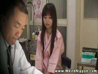Introvert aziatisch in doctors kantoor voor breast controleren omhoog
