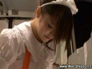 Ázijské čašníčka uses a hračka zatiaľ čo serving