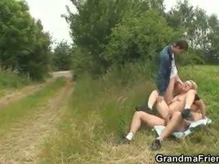 Slutty oma takes two cocks in de fields